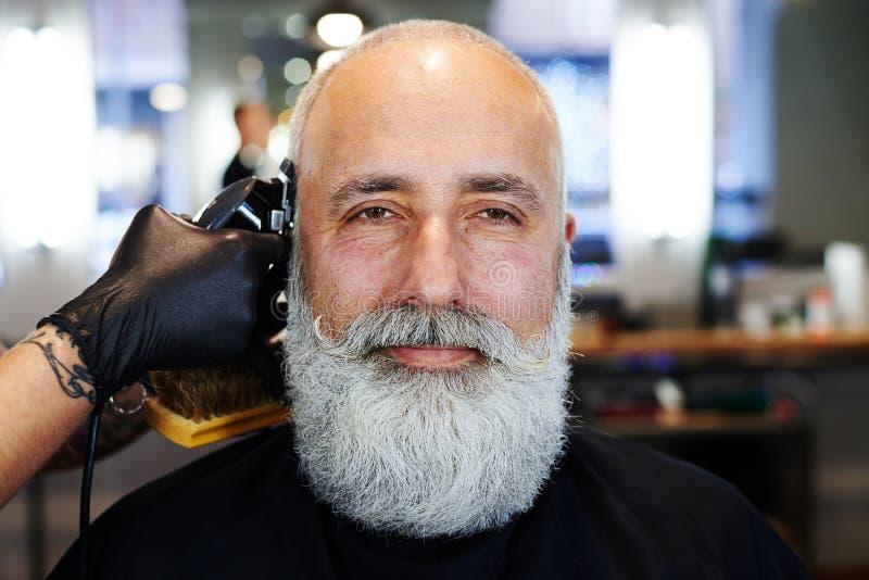 Homem superior considerável farpado no barbeiro fotografia de stock
