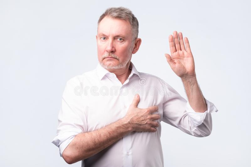 Homem superior considerável na camisa branca que faz um juramento Dê uma promessa imagens de stock