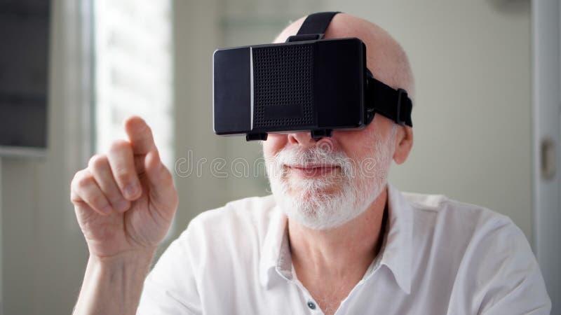 Homem superior considerável no branco usando VR 360 vidros em casa Fazer consulta e bate gestos foto de stock royalty free