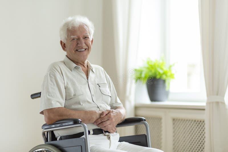 Homem superior de sorriso dos enfermos em uma cadeira de rodas apenas em casa fotos de stock royalty free