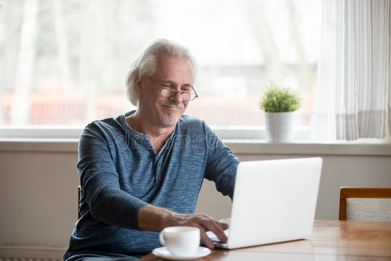Homem superior de sorriso no funcionamento de vidros no portátil em casa imagem de stock royalty free