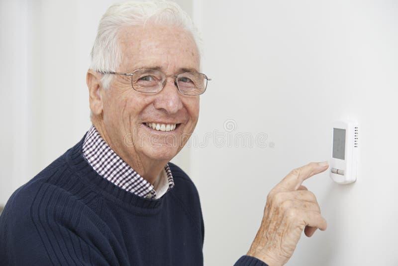 Homem superior de sorriso que ajusta o termostato do aquecimento central fotos de stock