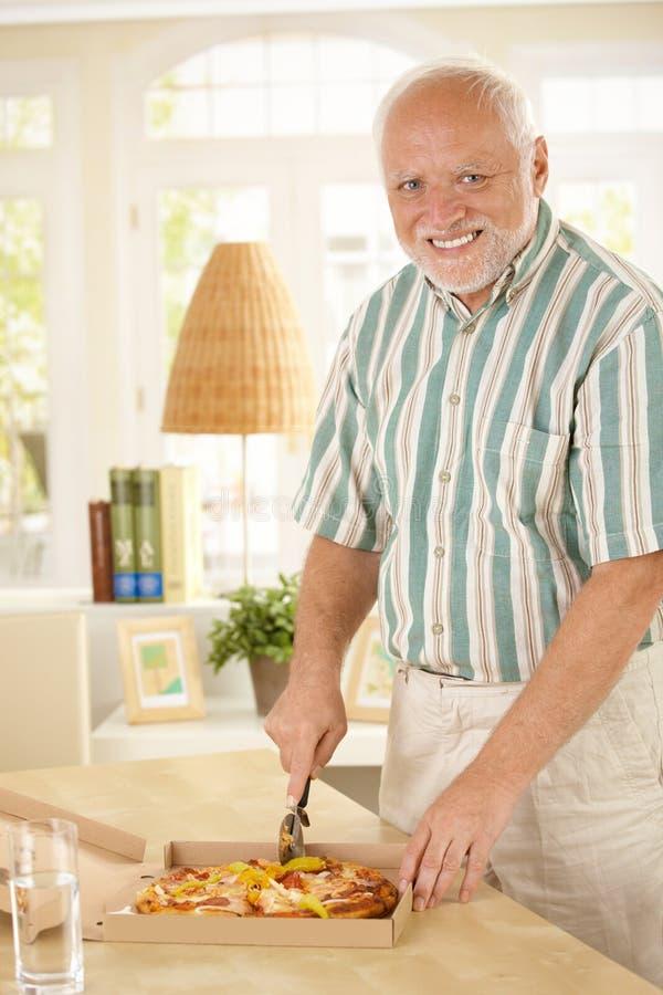 Homem superior de sorriso que corta acima a pizza imagem de stock royalty free