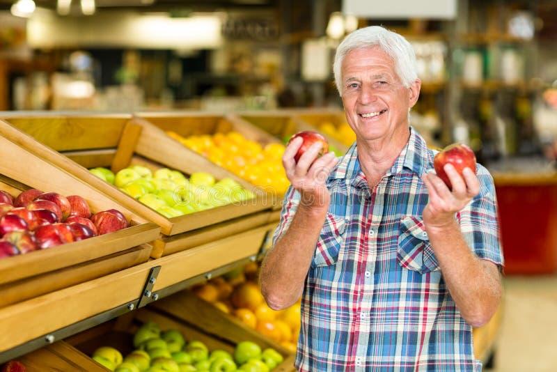 Homem superior de sorriso que guarda maçãs imagem de stock