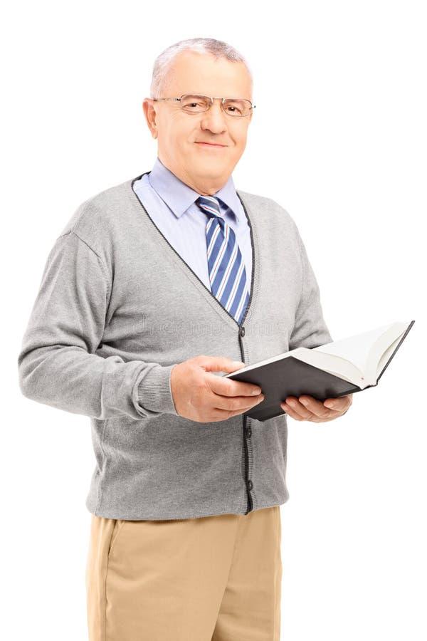 Homem superior de sorriso que lê um livro imagens de stock royalty free