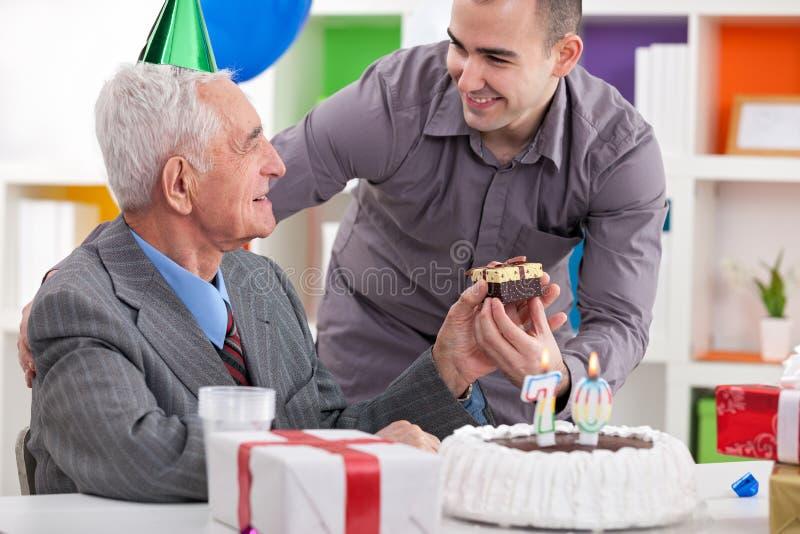 Homem superior de sorriso que recebe o presente para o aniversário imagens de stock