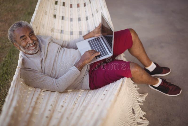 Homem superior de sorriso que usa o portátil ao relaxar na rede imagem de stock