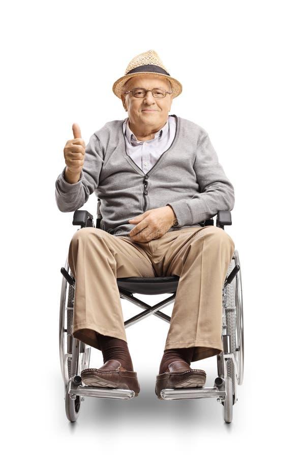 Homem superior deficiente em uma cadeira de rodas que olha a câmera e que mostra os polegares acima foto de stock
