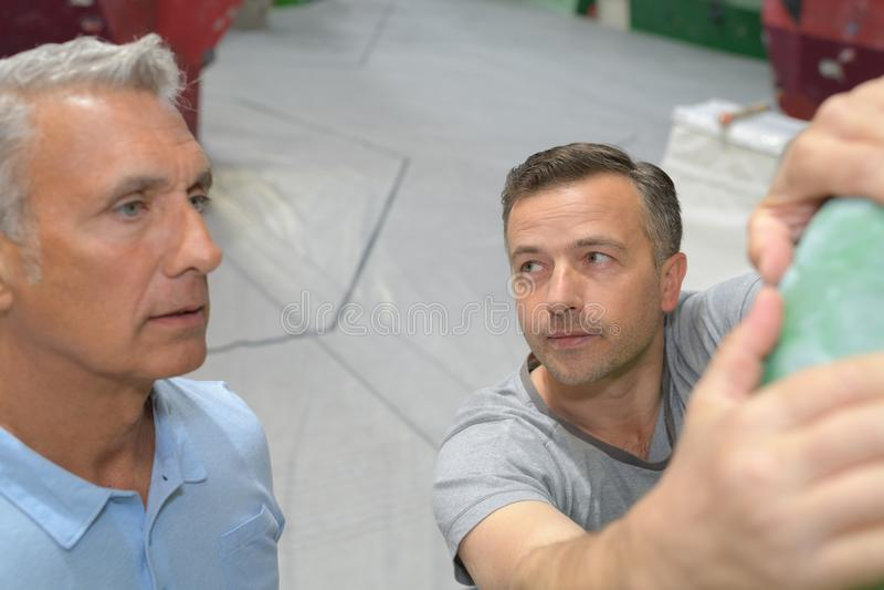 A homem superior do instrutor mostrando onde prender na parede de escalada foto de stock