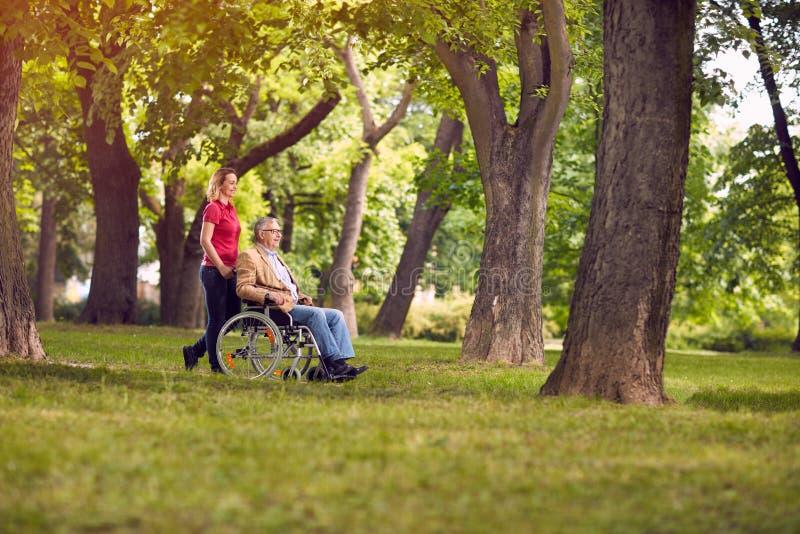 Homem superior do tempo feliz da família na cadeira de rodas e na filha no imagem de stock royalty free