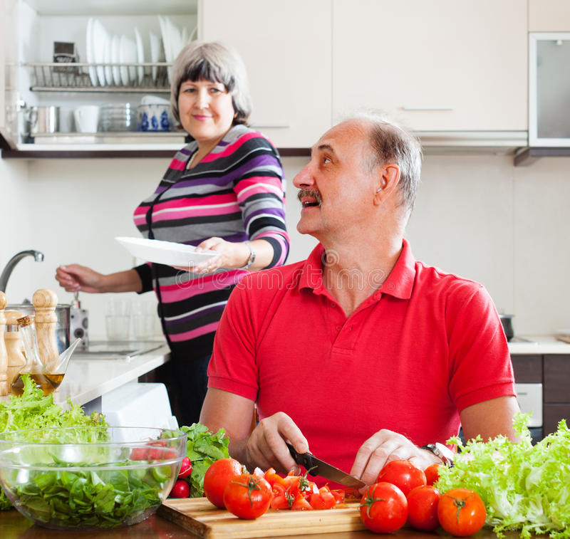 Homem superior e mulher madura na cozinha imagens de stock