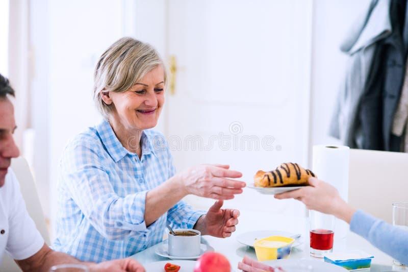 Homem superior e mulher que têm a manhã ensolarada do café da manhã fotografia de stock