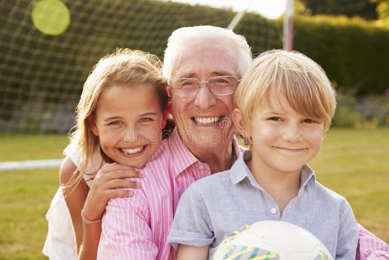 Homem superior e netos que guardam a bola que sorri à câmera foto de stock