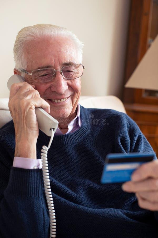Homem superior em casa que dá detalhes do cartão de crédito no telefone foto de stock royalty free