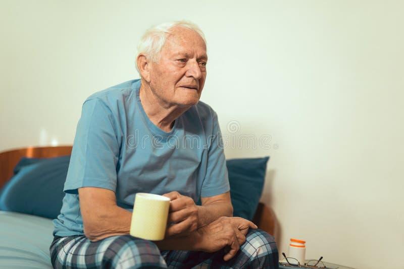 Homem superior em casa que guarda o copo do chá fotografia de stock royalty free