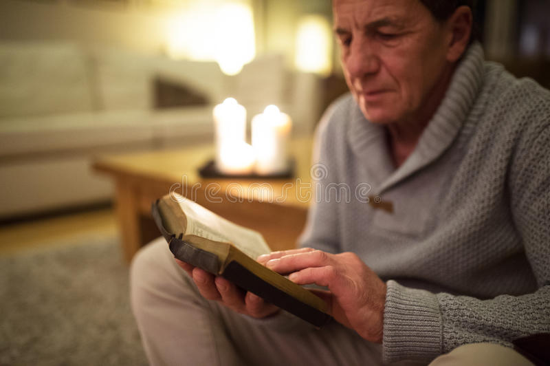 Homem superior em casa que lê a Bíblia, velas ardentes atrás dele fotos de stock royalty free