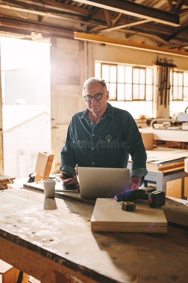 Homem superior em sua oficina da carpintaria fotografia de stock