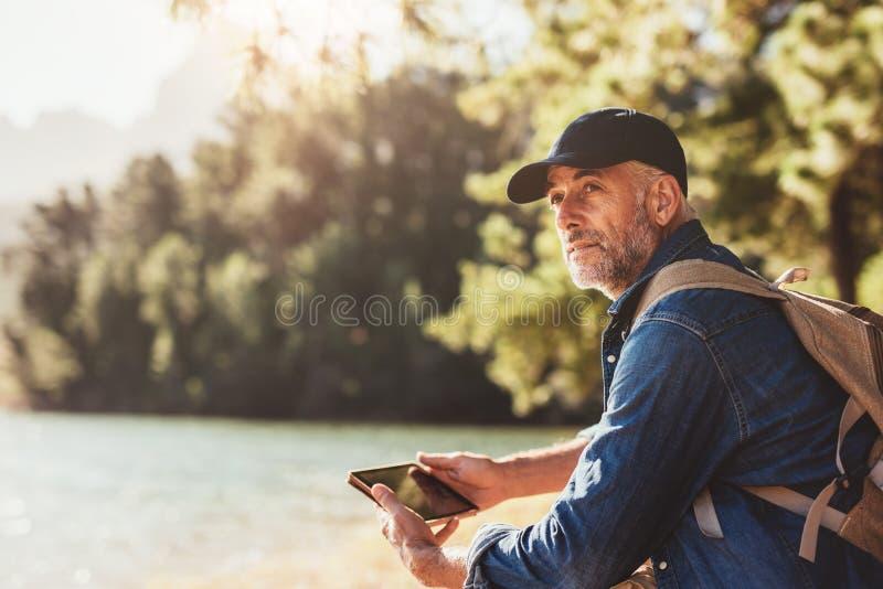 Homem superior em um lago com trouxa e a tabuleta digital imagem de stock