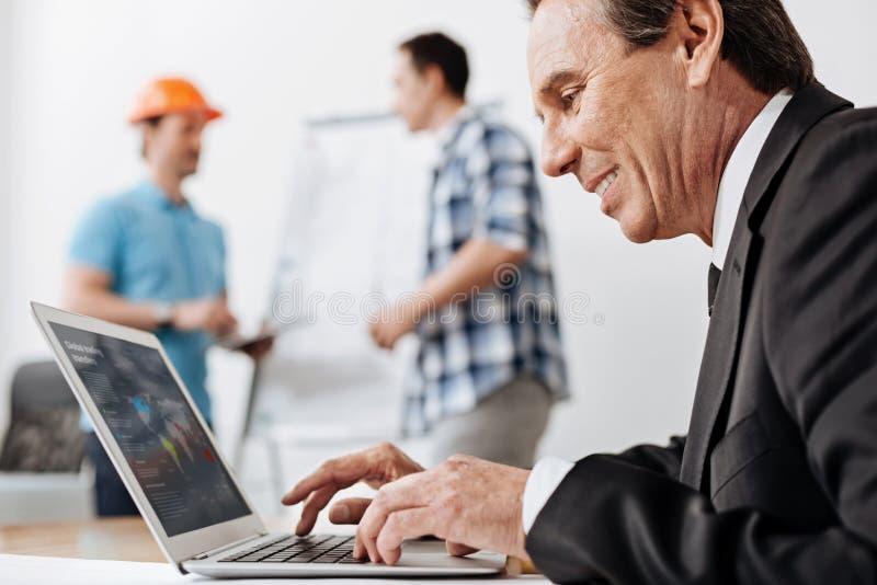 Homem superior em um terno que trabalha em seu portátil foto de stock royalty free