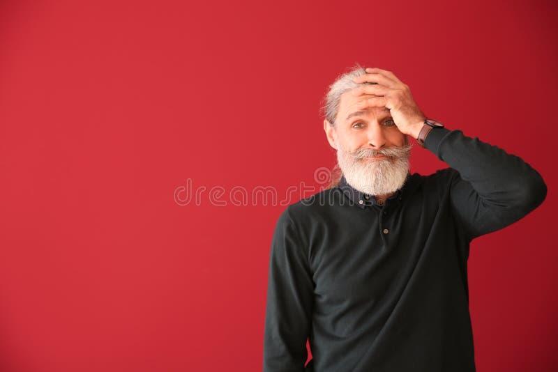Homem superior emocional após ter feito o erro no fundo da cor fotografia de stock