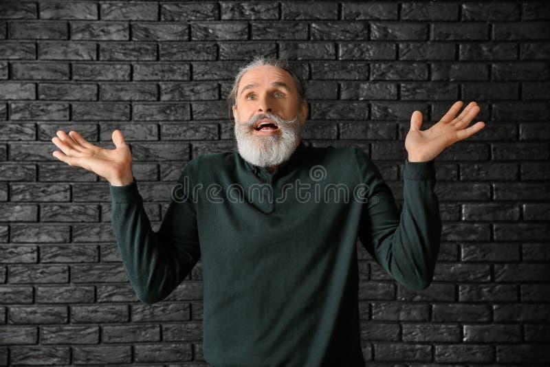 Homem superior emocional após ter feito o erro no fundo escuro imagem de stock
