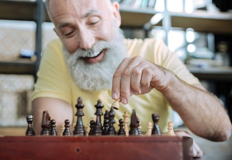 Homem superior extremamente feliz que joga a xadrez em casa fotos de stock