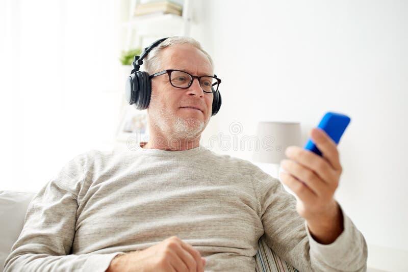 Homem superior feliz com smartphone e fones de ouvido imagens de stock