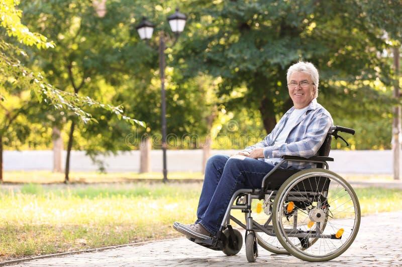Homem superior feliz na cadeira de rodas fora foto de stock royalty free