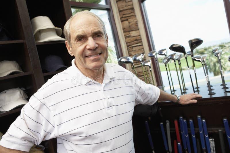 Homem superior feliz na loja do golfe imagens de stock royalty free