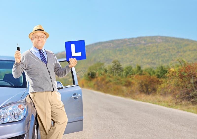 Homem superior feliz que levanta em seu carro, guardando um L sinal e a chave do carro fotografia de stock