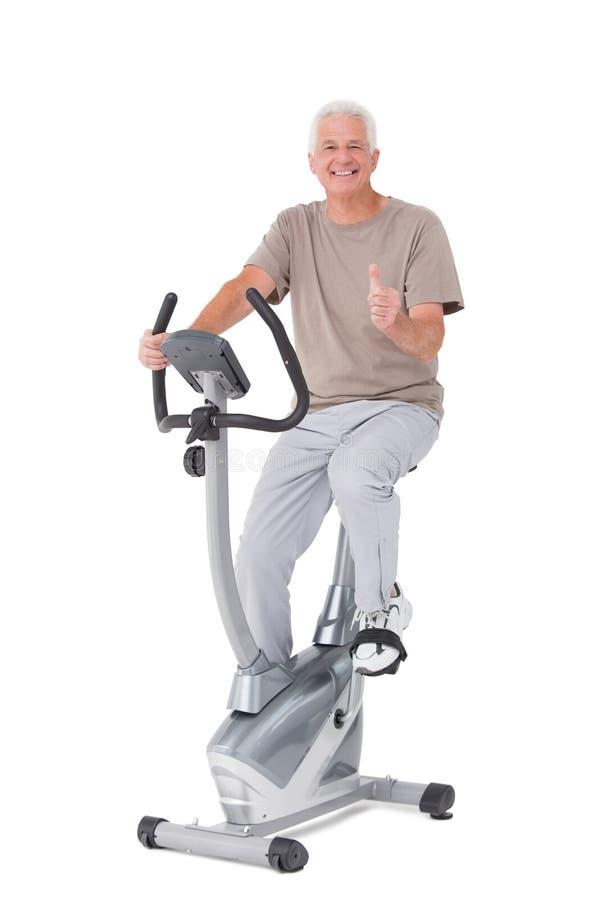 Homem superior na bicicleta de exercício fotografia de stock royalty free