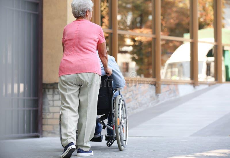 Homem superior na cadeira de rodas e na sua esposa na rampa fora foto de stock royalty free