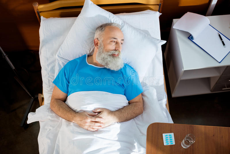 Homem superior na cama de hospital fotografia de stock royalty free