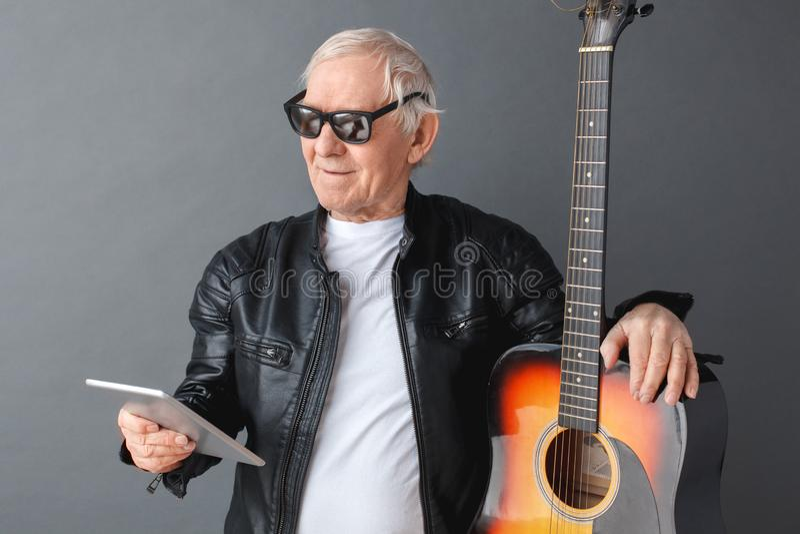 Homem superior na posição do casaco de cabedal e dos óculos de sol isolado no vídeo de observação de aperto cinzento da guitarra  foto de stock