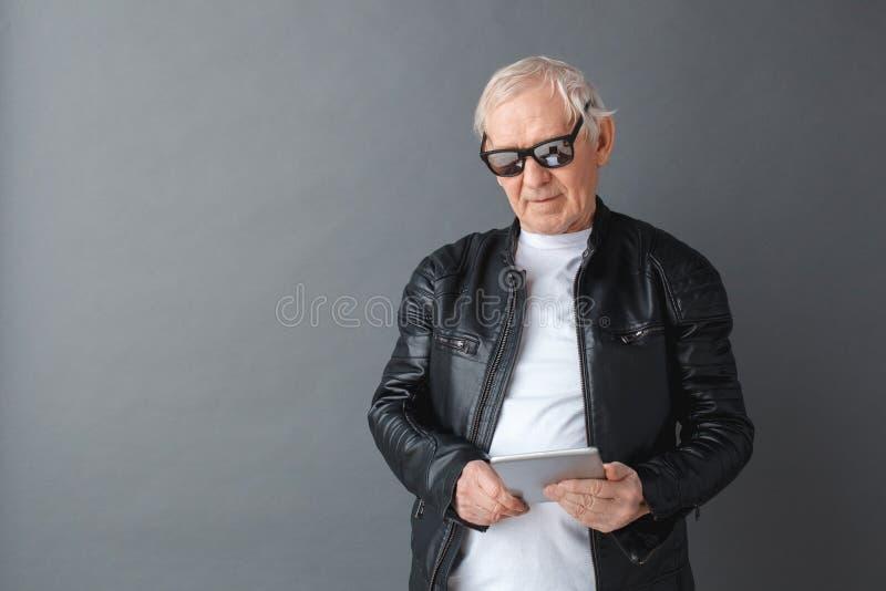 Homem superior na posição do casaco de cabedal e dos óculos de sol isolado no vídeo de observação cinzento na tabuleta digital co foto de stock