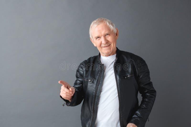 Homem superior na posição do casaco de cabedal isolado na câmera de vista pregando apontando cinzenta manhoso fotos de stock royalty free