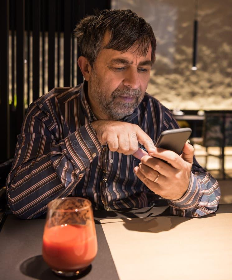 Homem superior na roupa ocasional usando o telefone celular imagens de stock