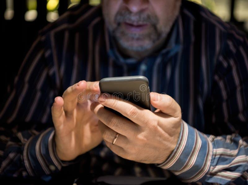 Homem superior na roupa ocasional usando o telefone celular foto de stock