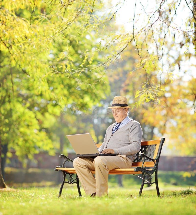 Homem superior no banco e trabalho em um portátil em um parque imagens de stock