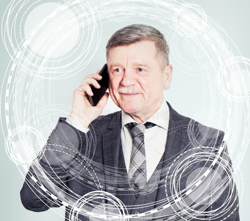 Homem superior no terno de negócio usando um telefone celular fotografia de stock