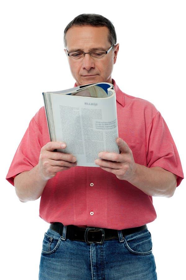Homem superior ocasional que lê um livro imagens de stock