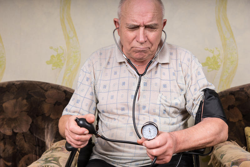 Homem superior olhando de sobrancelhas franzidas que monitora sua pressão sanguínea imagem de stock