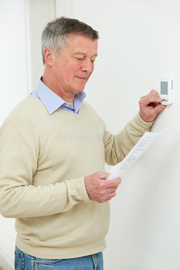 Homem superior preocupado que gira para baixo o termostato do aquecimento central fotos de stock royalty free