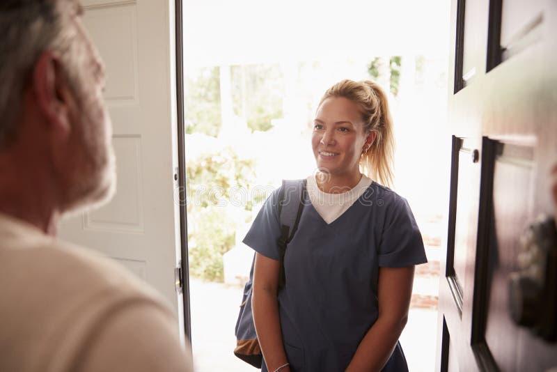 Homem superior que abre sua porta da rua a um trabalhador fêmea dos cuidados médicos que faz uma visita das saúdes ao domicílio imagem de stock royalty free