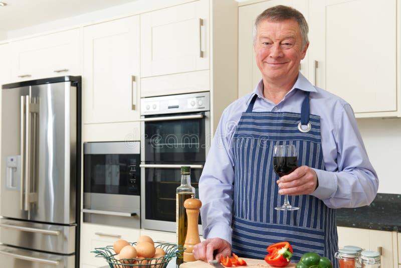Homem superior que aprecia o cozimento na cozinha com vidro do vinho foto de stock royalty free