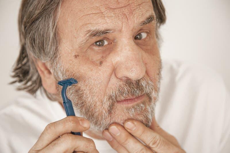 Homem superior que barbeia a barba no fundo branco fotos de stock