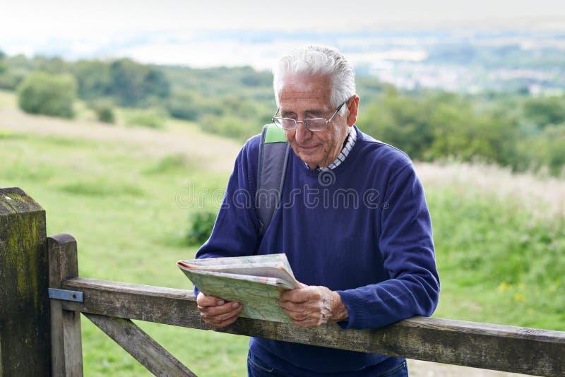 Homem superior que caminha no campo que olha o mapa foto de stock