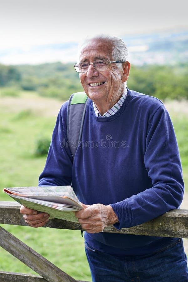 Homem superior que caminha no campo que olha o mapa imagem de stock royalty free