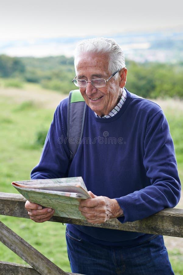 Homem superior que caminha no campo que olha o mapa fotos de stock