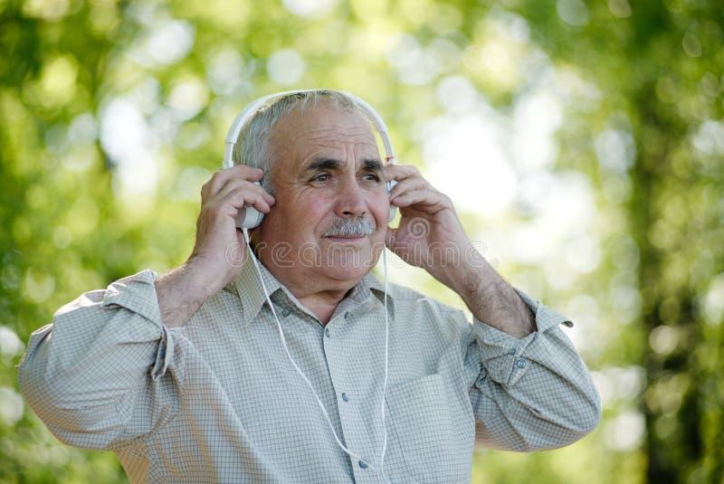 Homem superior que concentra-se em sua música imagem de stock